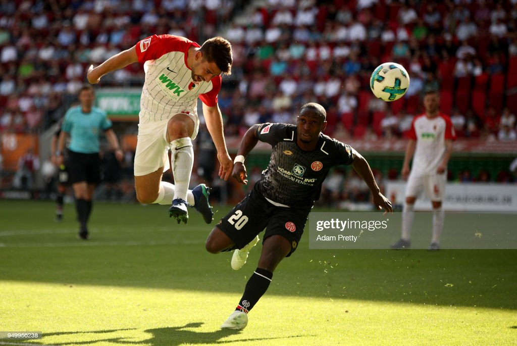 Rani Khedira (L) of Augsburg and Anthony Ujah of Mainz head for the ball during the Bundesliga match between FC Augsburg and 1. FSV Mainz 05 at WWK-Arena on April 22, 2018 in Augsburg, Germany.
