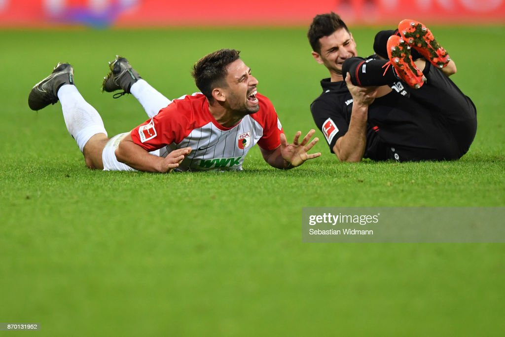 Rani Khedira of Augsburg and Lucas Alario of Bayer 04 Leverkusen react during the Bundesliga match between FC Augsburg and Bayer 04 Leverkusen at WWK-Arena on November 4, 2017 in Augsburg, Germany.