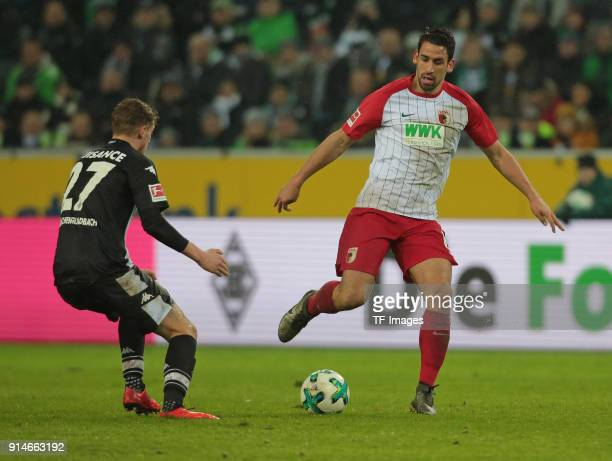 Rani Khedira of Augsburg and Mickael Cuisance of Moenchengladbach battle for the ball during the Bundesliga match between Borussia Moenchengladbach...