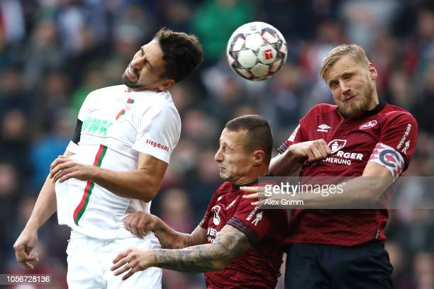 Rani Khedira of Augsburg attempts to win a header over Adam Zrelak of Nuernberg and Hanno Behrens of Nuernberg during the Bundesliga match between FC...