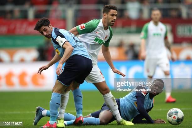 Rani Khedira of Augsburg is challenged by Lars Stindl and Denis Zakaria of Borussia Monchengladbach during the Bundesliga match between FC Augsburg...