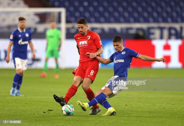 Rani Khedira of FC Augsburg is challenged by Can Bozdogan of FC Schalke 04 during the Bundesliga match between FC Schalke 04 and FC Augsburg at...