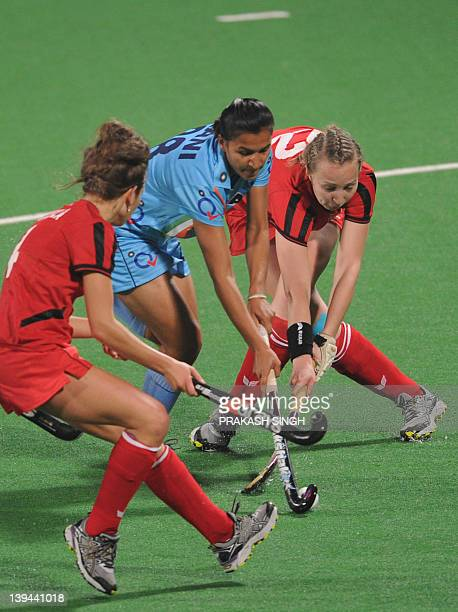 Rani Rampal of India attemps to maneuver past Amelia Katerla and Martyna Ggabara of Poland during the women's field hockey match between India and...