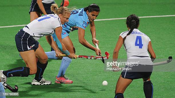 Rani Rampal of India dribbles past Agata Wybieralska and Dalila Mirabella of Italy during the women's field hockey match between India and Italy of...
