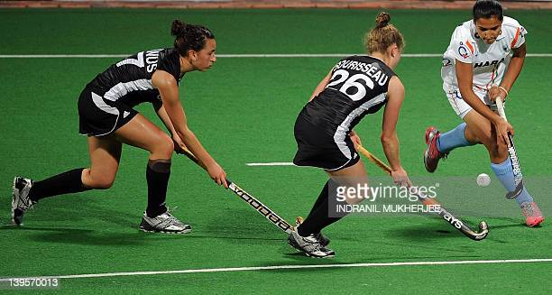 Rani Rampal of India dribbles past Natalie Sourisseau and Sara Mcmanus of Canada to score a goal during their women's field hockey match of the FIH...
