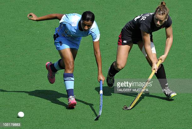 Rani Rampal of India fights for the ball with Katie Baker of Canada during their field hockey match at the Major Dhyan Chand National Stadium during...