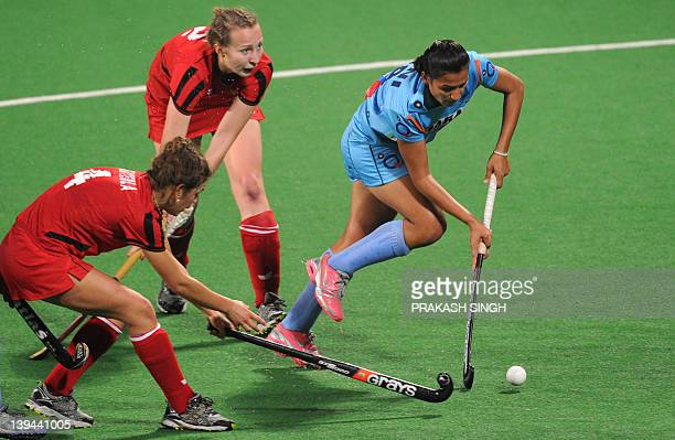 Rani Rampal of India maneuvers past Amelia Katerla and Martyna Ggabara of Poland during the women's hockey match between India and Poland of the FIH...