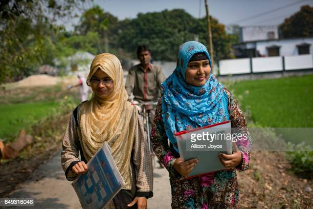 Rani walks with a friend with her father following on a bicycle to catch a rickshaw to take a school exam March 6 2017 in Khulna division Bangladesh...