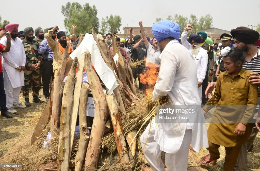 Ranjit Singh and Sahildeep Singh the brother and son of Indian Army soldier Paramjit Singh light his funeral pyre at Vein Pein village some 45 km...