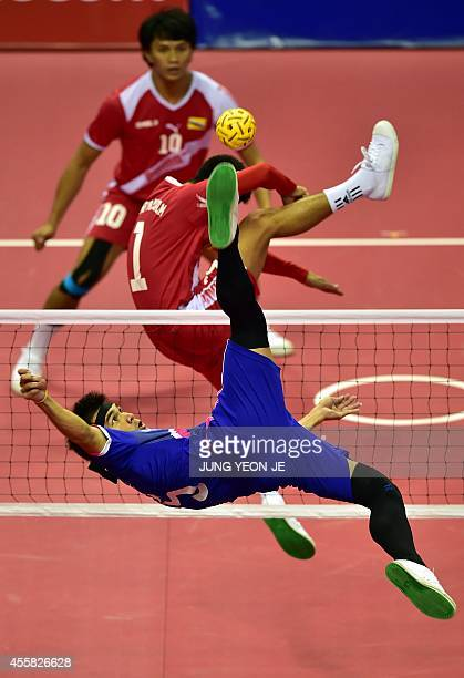 Raos' Noum Souvannalith strikes the ball against Brunei team in the men's double preliminary group B sepaktakraw match during the 2014 Asian Games at...
