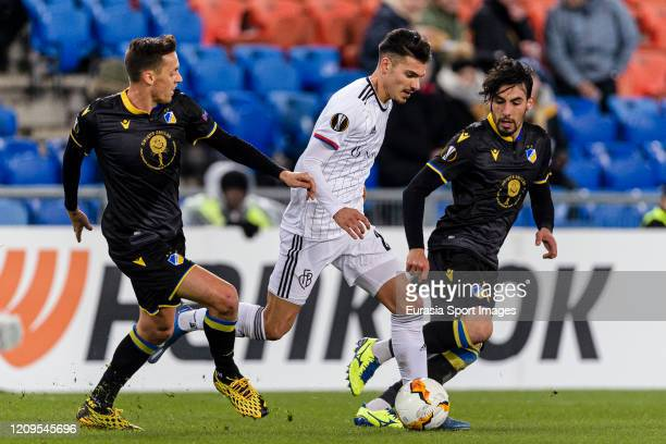 Raoul Petretta of Basel fights for the ball with Praxitelis Vouros of Apoel during the UEFA Europa League round of 32 second leg match between FC...