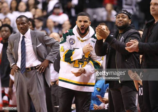 Rap artist Drake celebrates as head coach Dwane Casey of the Toronto Raptors looks on in the closing moments of their victory against the Washington...