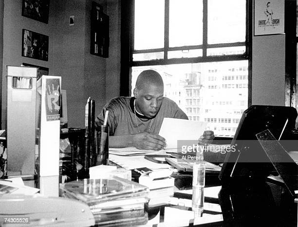 Rap artist JayZ sits at a desk and reads some papers in January 1996 in New York City New York