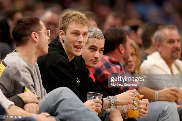 Rap artist Machine Gun Kelly watches the Denver Nuggets play the Charlotte Hornets in the first quarter at the Pepsi Center on January 5 2019 in...