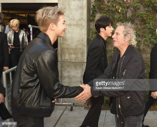Rap Monster of music group BTS greets American Music Awards producer Larry Klein during the 2017 American Music Awards at Microsoft Theater on...