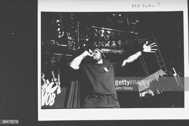 Rap singer Ice Cube singing into handheld mike as he performs on stage during the Lollapalooza '92 traveling rock fest cum carnival.