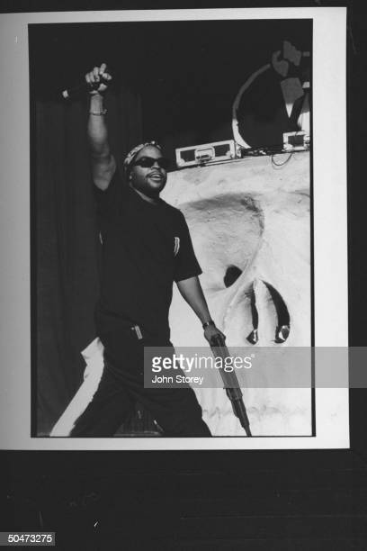 Rap singer Ice Cube waving mike high in the air on stage as he acknowledges unseen crowd at the Lollapalooza '92 traveling rock fest cum carnival