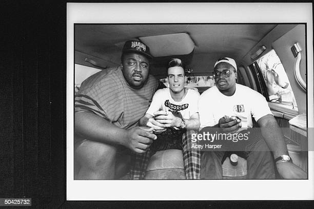 Rap singer Vanilla Ice sitting between his bodyguards Big E Chilly in back seat of limousine during publicity tour