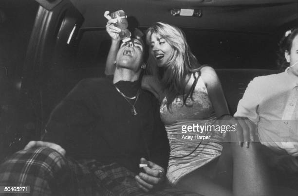Rap star Vanilla Ice having honey poured down his throat by model Rowanne Brewer in the back of a limo