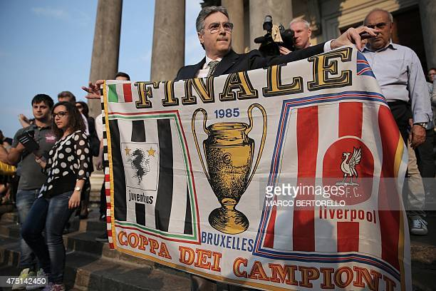 Raphael Desantis a survivor of the Heysel tragedy holds a flag from the match ahead of a mass at Gran Madre di Dio church in Turin on May 29 to mark...