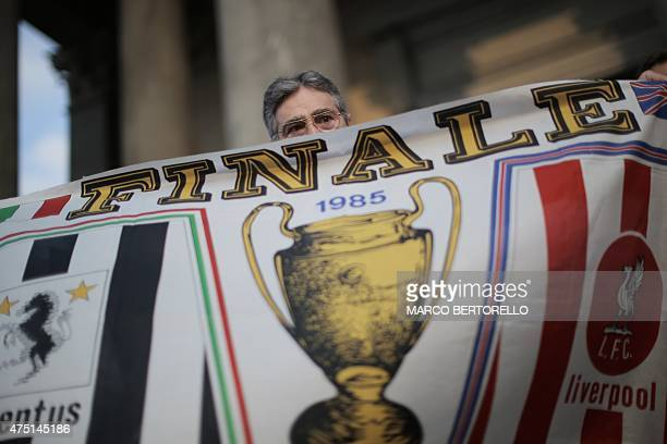 Raphael Desantis, a survivor of the Heysel tragedy, holds a flag from the 1985 European Cup Final match ahead of a mass at Gran Madre di Dio church...