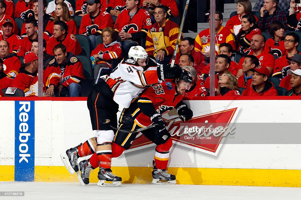 Raphael Diaz #33 of the Calgary Flames is checked Nate Thompson #44 of the Anaheim Ducks at Scotiabank Saddledome for Game Four of the Western Quarterfinals during the 2015 NHL Stanley Cup Playoffs on May 8, 2015 in Calgary, Alberta, Canada.