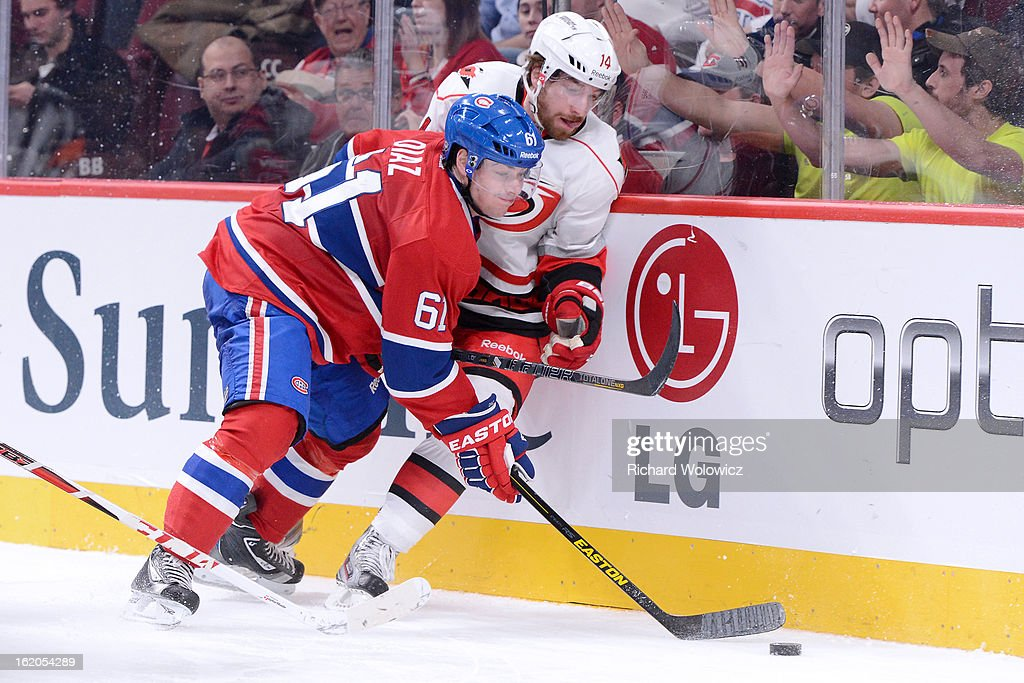 Raphael Diaz #61 of the Montreal Canadiens and Andreas Nodl #14 of the Carolina Hurricanes battle for the puck during the NHL game at the Bell Centre on February 18, 2013 in Montreal, Quebec, Canada. The Canadiens defeated the Hurricanes 3-0.