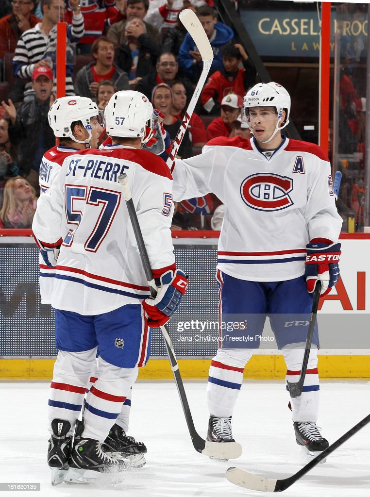 Raphael Diaz #61 of the Montreal Canadiens celebrates a third period goal with teammates Martin St. Pierre #57 and Gabriel Dumont #37 during an NHL pre-season game against the Ottawa Senators at Canadian Tire Centre on September 25, 2013 in Ottawa, Ontario, Canada.