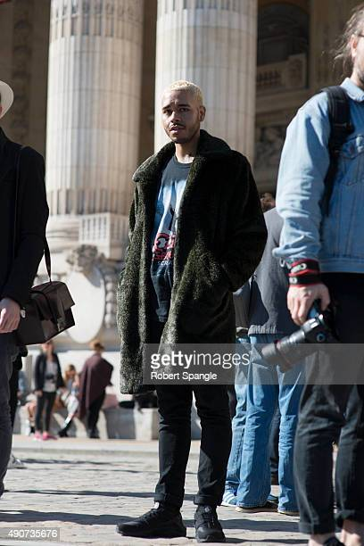Raphael Figueroa wears vintage green fur overcoat distressed band tshirt and black nike hourache sneakers before Guy Laroche at the Grand Palais...