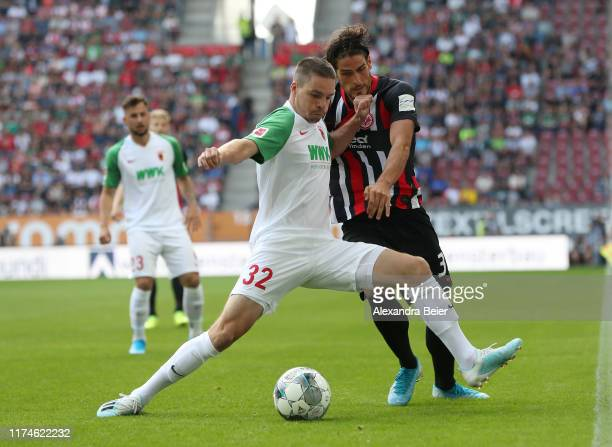 Raphael Framberger of FC Augsburg fights for the ball with Goncalo Paciencia of Eintracht Frankfurt during the Bundesliga match between FC Augsburg...