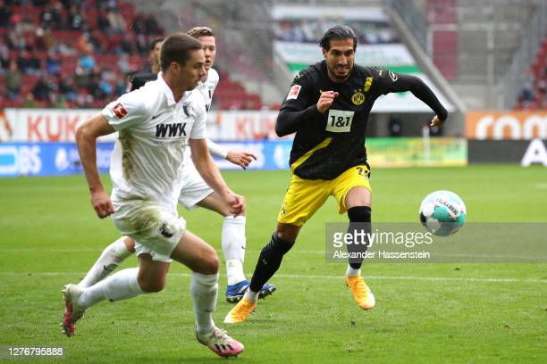 Raphael Framberger of FC Augsburg is challenged by Emre Can of Borussia Dortmund during the Bundesliga match between FC Augsburg and Borussia...