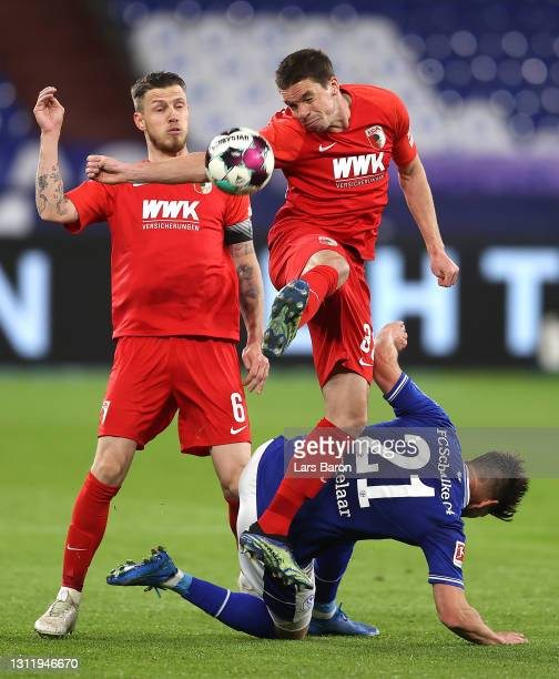 Raphael Framberger of FC Augsburg is challenged by Klaas-Jan Huntelaar of FC Schalke 04 during the Bundesliga match between FC Schalke 04 and FC...