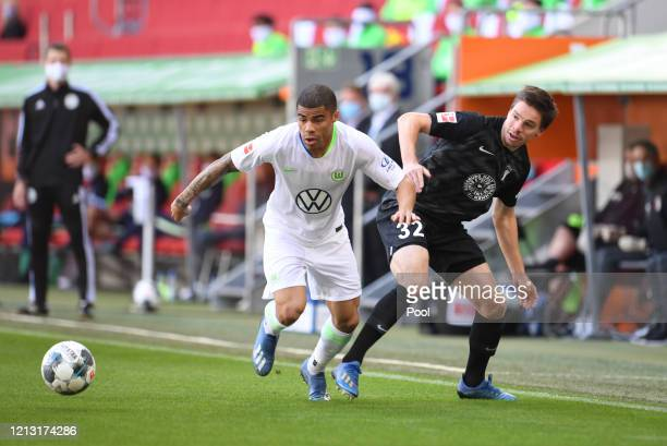 Raphael Framberger of FC Augsburg is challenged by Paulo Otavio of VfL Wolfsburg during the Bundesliga match between FC Augsburg and VfL Wolfsburg at...