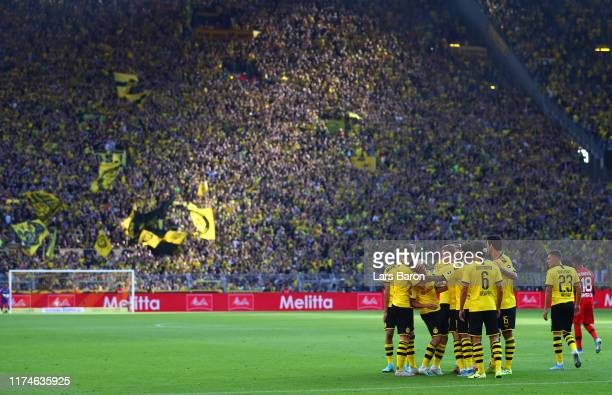 Raphael Guerreiro of Borussia Dortmund celebrates after scoring his team's third goal with team mates during the Bundesliga match between Borussia...