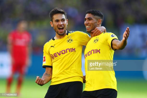 Raphael Guerreiro of Borussia Dortmund celebrates after scoring his team's third goal with team mate Achraf Hakimi during the Bundesliga match...
