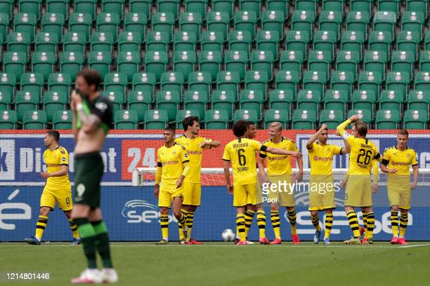 Raphael Guerreiro of Borussia Dortmund celebrates with team mates after he scores his sides first goal during the Bundesliga match between VfL...