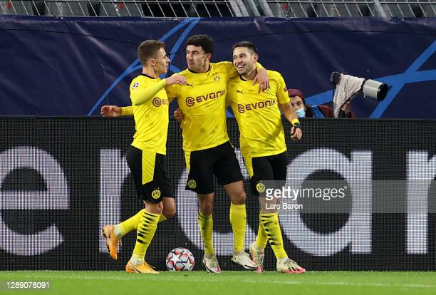 Raphael Guerreiro of Borussia Dortmund celebrates with teammates Thorgan Hazard and Giovanni Reyna after scoring their team's first goal during the...