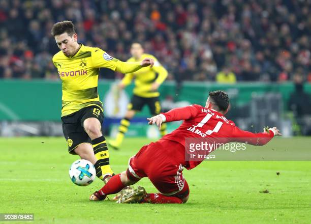 Raphael Guerreiro of Dortmund and James Rodriguez of Muenchen battle for the ball during the DFB Cup match between Bayern Muenchen and Borussia...