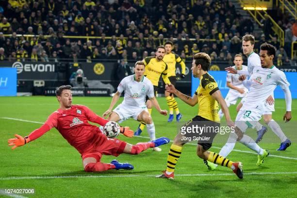 Raphael Guerreiro of Dortmund battles for the ball with Goalkeeper Jiri Pavlenka of Bremen during the Bundesliga match between Borussia Dortmund and...