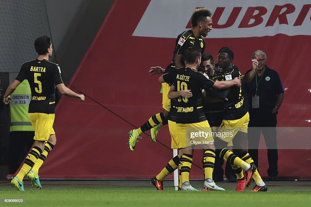 Raphael Guerreiro (C) of Dortmund celebrates scoring the opening goal with his team mates during the Bundesliga match between VfL Wolfsburg and Borussia Dortmund at Volkswagen Arena on September 20, 2016 in Wolfsburg, Germany.