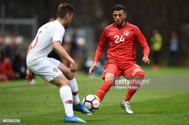 Raphael Guerreiro of Portugal competes for the ball with Anice Badri of Tunisia during the international friendly football match against Portugal and...
