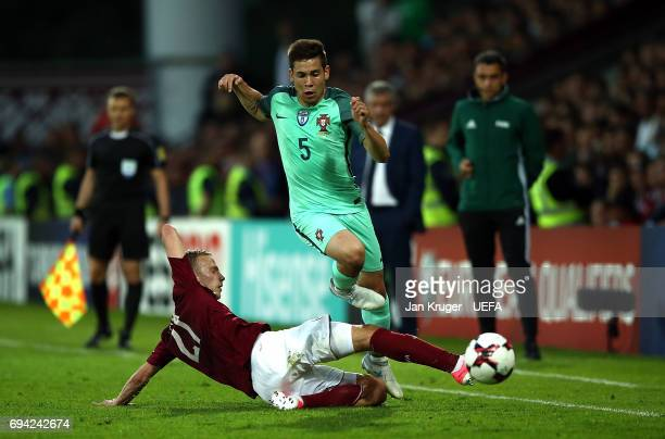 Raphael Guerreiro of Portugal is tackled by Glebs Kluskins of Latvia during the FIFA 2018 World Cup Qualifier between Latvia and Portugal at Skonto...