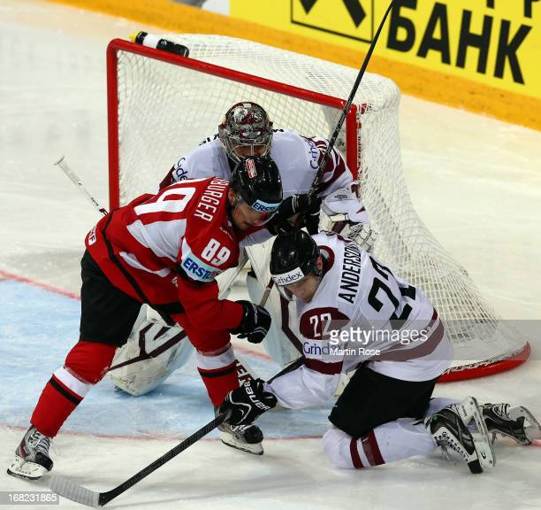 Raphael Herburger of Austria and Janis Andersons of Latvia battle for the puck during the IIHF World Championship group H match between Austria and...