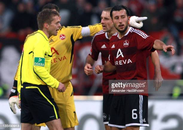Raphael Schaefer , keeper of Nuernberg talks with his team mates Dominic Maroh and Timmy Simons to referee Dr. Jochen Drees during the Bundesliga...
