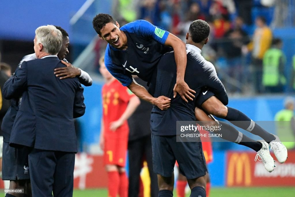 TOPSHOT - Raphael Varane (top) celebrates as he is carried by France's defender Presnel Kimpembe at the end of the Russia 2018 World Cup semi-final football match between France and Belgium at the Saint Petersburg Stadium in Saint Petersburg on July 10, 2018. (Photo by CHRISTOPHE SIMON / AFP) / RESTRICTED