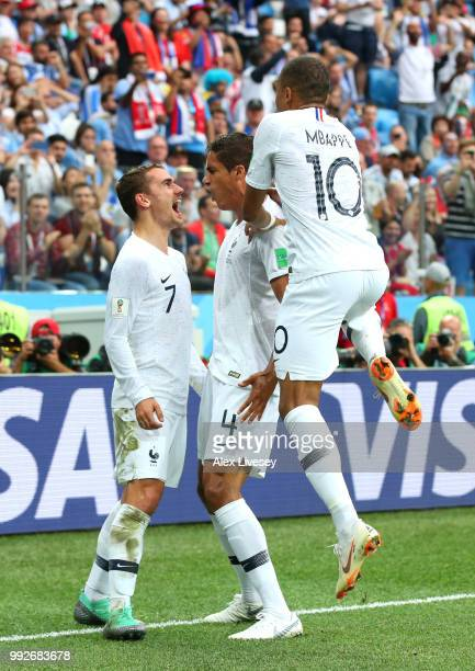 Raphael Varane of France celebrates with team mates Kylian Mbappe and Antoine Griezmann after scoring his team's first goal during the 2018 FIFA...