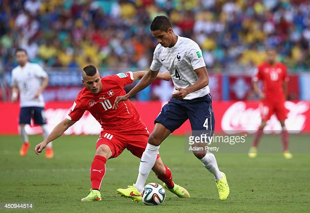 Raphael Varane of France controls the ball against Granit Xhaka of Switzerland during the 2014 FIFA World Cup Brazil Group E match between...