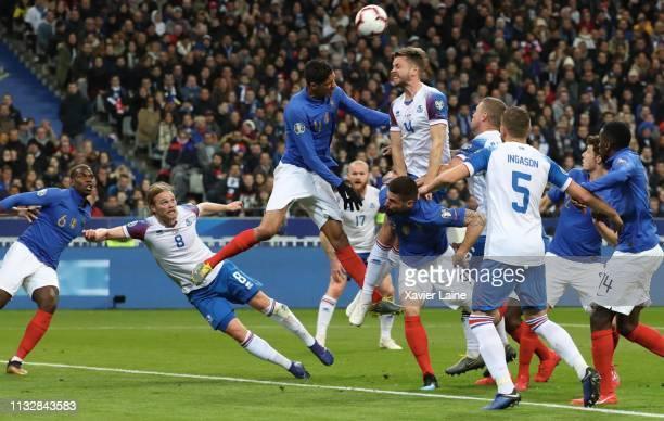 Raphael Varane of France kick the ball over Kari Arnason of Iceland during the 2020 UEFA European Championships Group H qualifying match between...