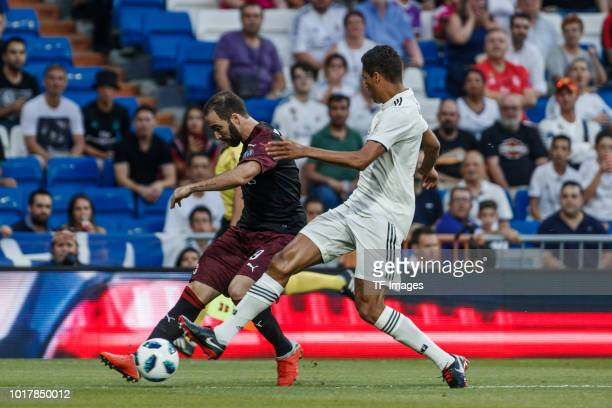 Raphael Varane of Real Madrid and Gonzalo Higuain of AC Milan battle for the ball during the Santiago Bernabeu trophy match between Real Madrid and...