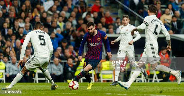 Raphael Varane of Real Madrid and Lionel Messi of Barcelona battle for the ball during the La Liga match between Real Madrid CF and FC Barcelona at...